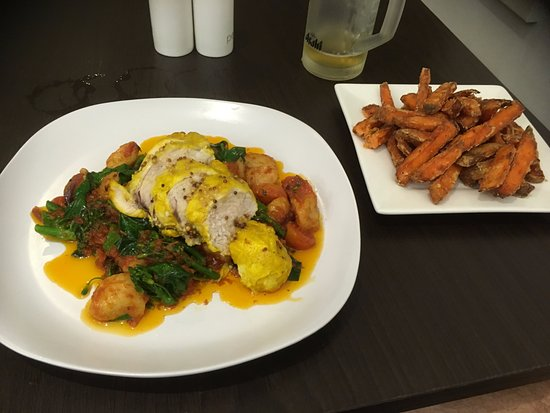 Rockhampton, Australia: saffron chicken with gnocchi and a side of sweet potato fries. Asahi Beer on tap too.