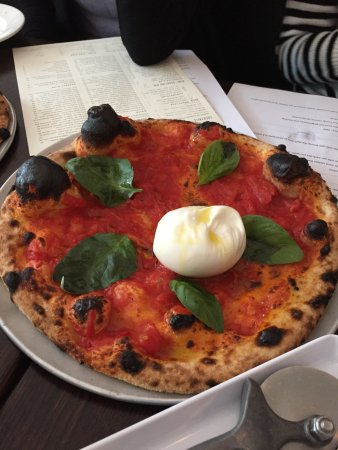 The burrata pizza before breaking it open and spreading it all out.