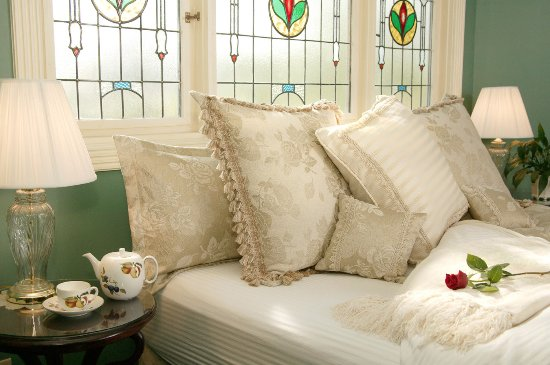 The Inn at Rose Hall Bed and Breakfast: Luxurious king bed in the Grand Tiffany Tower surrounded with antique stained-glass.