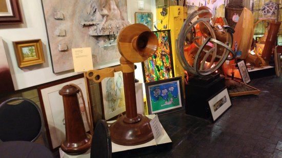 Artisanworks: Wood carved phone and iron in the background plus other artifacts.