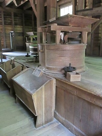 Great Smoky Mountains National Park, Carolina do Norte: Mill gringstone in operation. Cornmeal going into the bin.