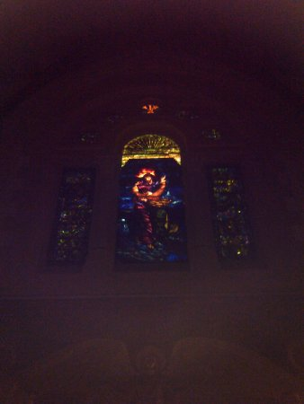 Willard Chapel: Large stained glass window at back of chapel flanked by two smaller windows.