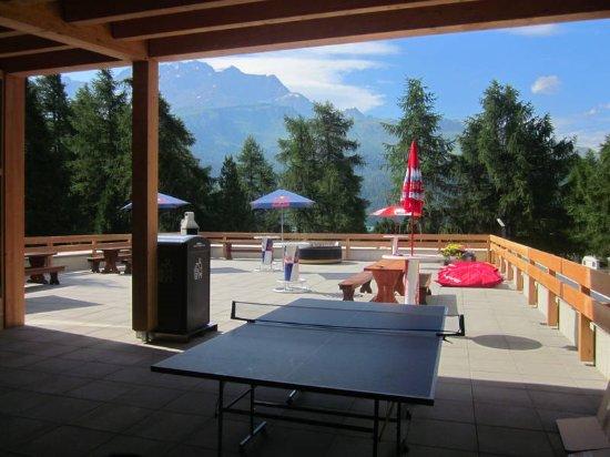 Silvaplana, Switzerland: Campinggebäude - Terrasse mit Tischtennisplatte, Tischfussball und Grill.