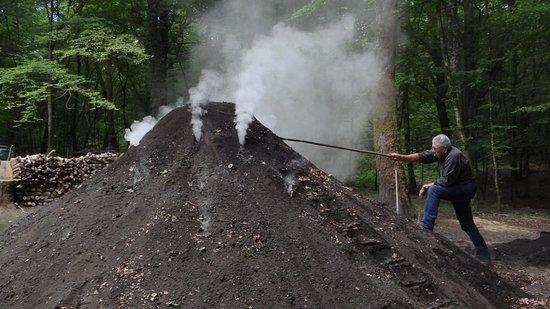 Baraques du 14: Un des charbonniers amateurs régule la carbonisation