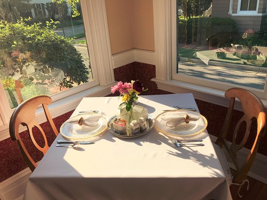 Hummingbird Inn: A romantic table for two surrounded by windows with view of historic neighborhood