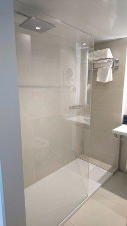Salle de bain avec toilettes et douche à l\'italienne. Serviettes ...