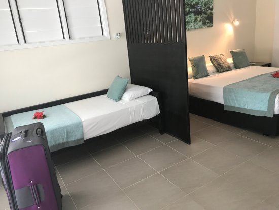 Treasure Island Resort: King bed and single bed with a privacy screen.
