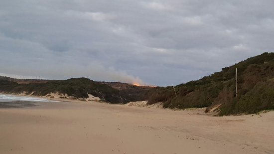 Crawford's Beach Lodge: sun rise on the beach with a bit of burning off in the background