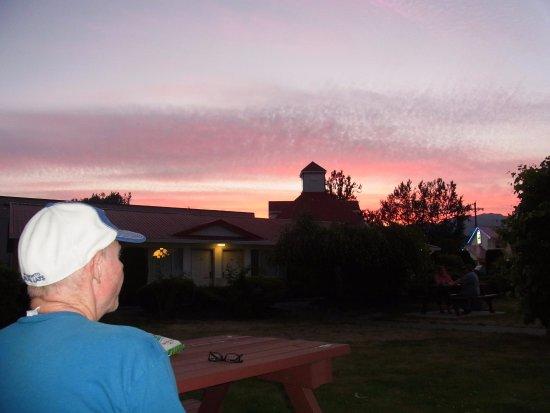 Rainbow Motor Inn: 庭のベンチ・テーブルから見た夕焼け空