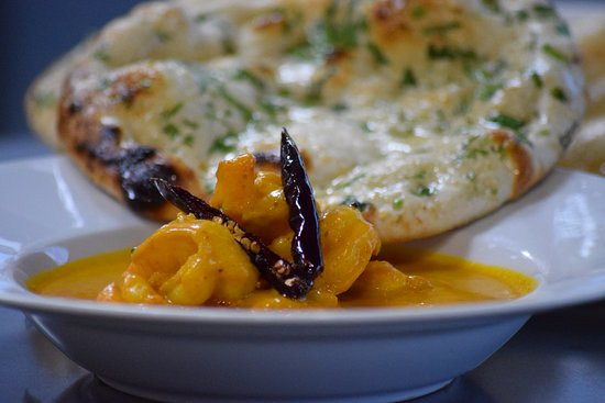 Goan Prawn Curry Black tiger prawns cooked in coastal spices, finished with coconut milk & vineg