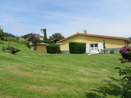 Soto de Luina, Spanien: Vista general del jardín y edificio de apartamentos