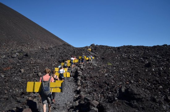 Quetzaltrekkers - Day Tours: The walk up to the summit of Cerro Negro carrying our packs and boards