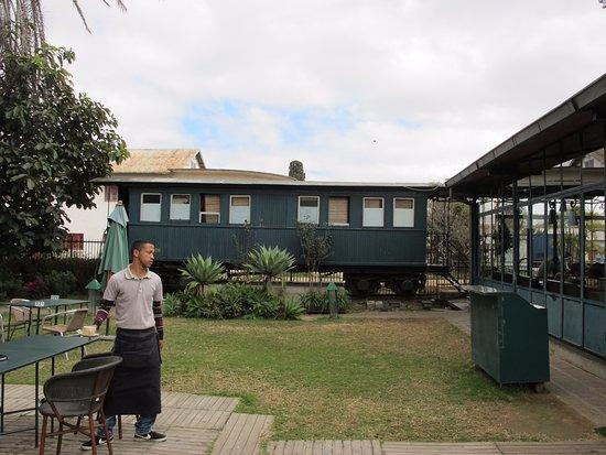 Cafe de la Gare: Le jardin et en arrière plan les toilettes dans le wagon.