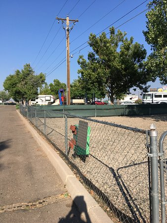 American RV Resort: Dog yard with children's play area in background.