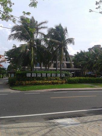 Yin Yuan Holiday Resort: Это вид с дороги, за кустиками сразу бассейн, сзади нас море.