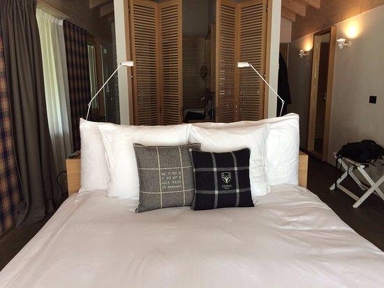 CERVO Zermatt: Bett, dahinter Pult und Badezimmer