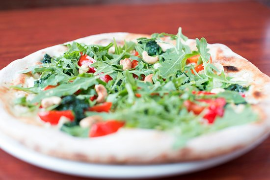 Cucinos Italian Restaurant: Pizza base topped only with goats cheese, cashew nuts, rocket and spinach leaves, red peppers dr