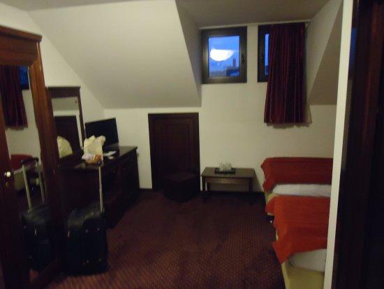 Sacele, Romania: Widok obszernego pokoju z wygodnymi łóżkami i dużą szafą .