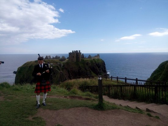 Stonehaven, UK: Man playing Bag Pipes! before entering the castle