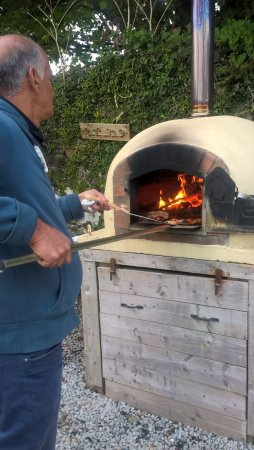 Kilkhampton, UK: Cooking our home-made pizzas in the clay oven.