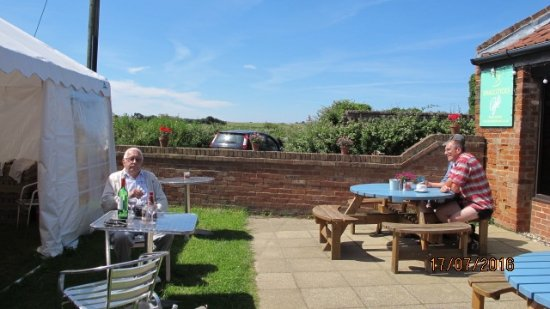 Happisburgh, UK: Outside seating area of Smallsticks Cafe - Happisburgh Lighthouse in the distance.