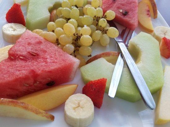 Huge fruit salad arranged artfully on the plate.