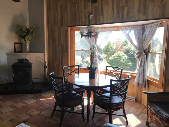 Hither House Cottages : East/West Cottage Dining area with a wood burning fireplace.