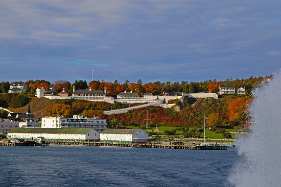 """Mackinaw City, MI: Mackinac Island and Fort Mackinac with Star Lines' traditional """"Rooster Tail"""" behind the boat."""