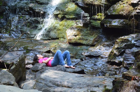 Mountain Rest, Carolina del Sur: An unidentified hiker naps along the rocks at Yellow Branch Falls
