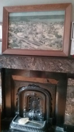 Hamilton Guesthouse: Fireplace in the living room with historic images of Hamlton