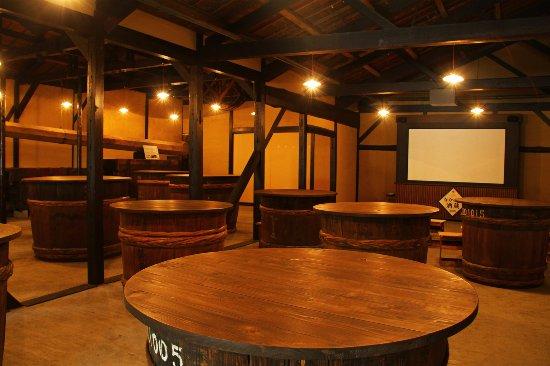 NAKANO.B.C.: 杉樽を使用したテーブルが並ぶ、ムード溢れる長久BAR。こちらでは日本酒造りについての映像をご覧頂けます。