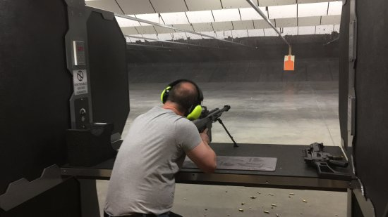 Murray, UT: Firing a Barrett 50 cal BMG at a target 25 yards away. A full auto G36 is resting on the bench.