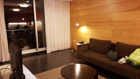 Costa Colonia Riverside Boutique Hotel: la suite tiene estar, dormitorio y area de cocina con platos, vasos y tazas para 3 personas.