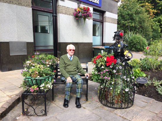 Pitlochry, UK: A scottish gentleman by the lady in flowers!