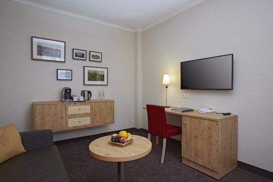 H+ Hotel & SPA Friedrichroda: Wohnbereich mit Schreibtisch, Fernseher und Kaffee& Teestation in der Suite Spiessberg