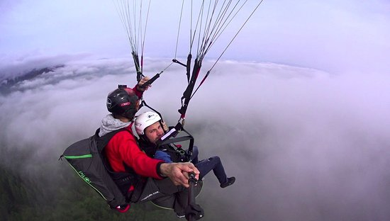 Paragliding flight over clouds in Bunloc, Sacele