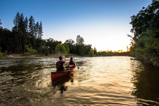 Lotus, CA: Marriage retreat participants take a canoe ride into the sunset