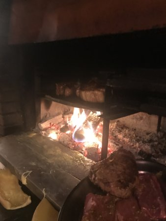 Evolene, سويسرا: The wood grill, the raclette is melting ready to scoop up.