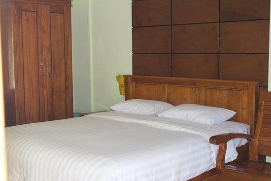 Global Inn Juanda: Kamar deluxe dengan kursi kayu