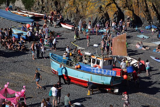 Cadgwith, UK: The beach on regatta day with a local fishing boat being winched through the crowds.