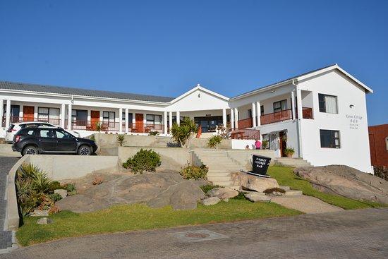 Das Cottage mit den Eingängen und den Parkplätzen (links)