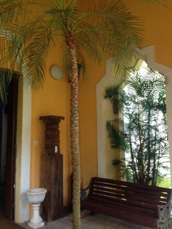 Sangolda, India: Kadamba Pillar , Moghul planter & Cast iron & mahogany wood garden bench.