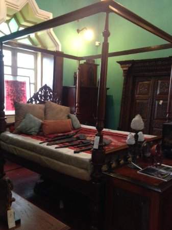 Sangolda, India: Teakwood four poster bed with a caucasian kelim spread and ceremonial spoon from Kerala laid out