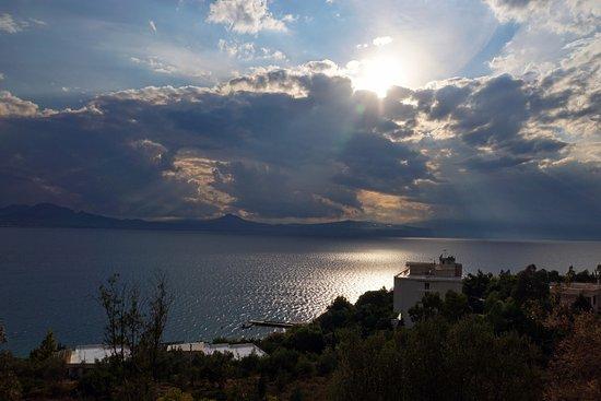 Loutraki, Grækenland: Солнце в облаках над заливом