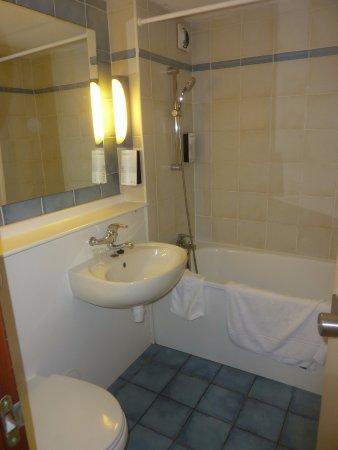 La salle de bains pourvue d\'une petite baignoire avec douche ...