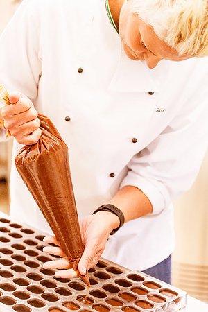 Kettering, Australia: Hand filling praline chocolates.