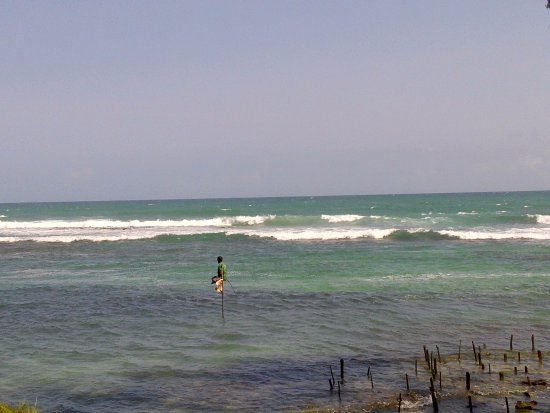 Turtle Eco Beach: a lonely fisherman on stick in front on TurtleEcoBeach