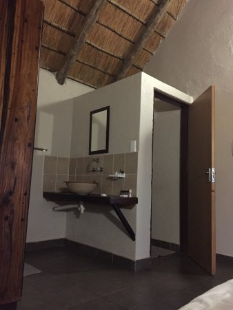 Malelane, Zuid-Afrika: Toilet inside door area. Shower across from sink. Gecko under middle ceiling rafter (to the righ