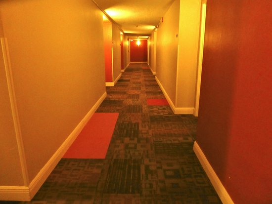 Inn of Naples: Hallway a little dark. Decorated in golds and rusts.
