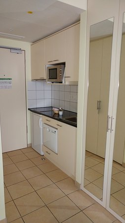 Citadines München Arnulfpark: Kitchen area- microwave, hob, dishwasher and fridge
